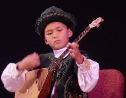 A young boy playing the dombra