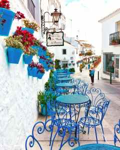 The Ferryman's Daughter Seaside cafe blue chairs flower pots Cornwall