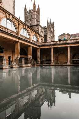 old temple facade reflecting in roman baths in england